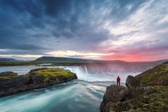 Landscape of Iceland with Godafoss waterfall. Godafoss waterfall. Beautiful landscape in Iceland. Man in red jacket standing on the rock and looking at the dawn Stock Images