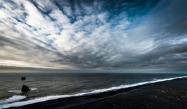 Landscape in Iceland with Ocean Water, Rocks and Black Sand Beach. Royalty Free Stock Photography