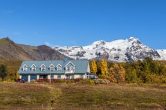 Landscape with an icelandic home and snowy mountains in the back Stock Photography