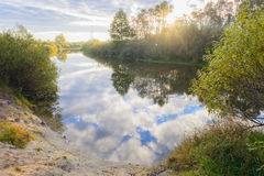The landscape illuminated by the rays of the morning autumn sun. In the mirror surface waters of the river reflected clouds and blue sky Stock Photo