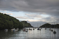 Landscape image of boats moored in harbour in Devon at sunrise Stock Image