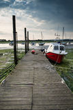 Landscape image of boats mored to jetty in harbor during Summer Royalty Free Stock Photography
