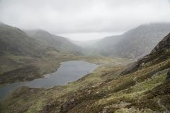 Landscape image of Llyn Idwal in Glyders mountain range in Snowd. Moody landscape image of Llyn Idwal in Glyders mountain range in Snowdonia during heavy royalty free stock images