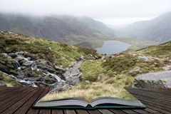 Landscape image of Llyn Idwal in Glyders mountain range in Snowdonia during heavy rainfall in Autumn coming out of pages of open. Moody landscape image of Llyn stock photo