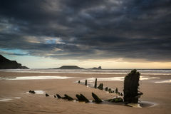 Landscape Image Of Old Shipwreck On Beach At Sunset In Summer Stock Photos