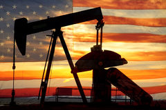 American Oil. Landscape image of a oil well pumpjack wiith an early morning golden sunrise and American USA red White and Blue Flag background Royalty Free Stock Photos
