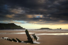 Landscape image of old shipwreck on beach at sunset in Summer. Landscape image of shipwreck on beach at sunset in Summer Stock Photography