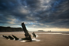 Landscape image of old shipwreck on beach at sunset in Summer Stock Image