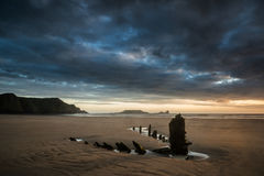 Landscape image of old shipwreck on beach at sunset in Summer Stock Photography