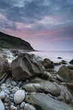 Landscape image of rocky beach and cliffs at sunrise. Landscape image of rocky beach at sunrise Stock Images