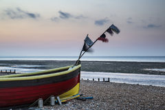 Landscape image of small fishing boats on beach at sunrise in Sp Stock Photography