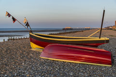 Landscape image of small fishing boats on beach at sunrise in Sp Stock Images