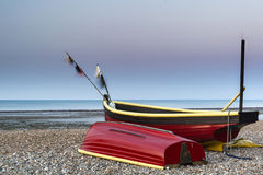 Landscape image of small fishing boats on beach at sunrise in Sp Stock Photo