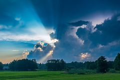 Landscape image of sunset with sun rays. Cloudy sunset with sun rays stock photography