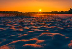Landscape image of a sunset at winter with beautiful snow mounds royalty free stock photo