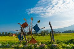 Landscape images of Turbine baler. Landscape images of The turbine baler is close to the rice fields, with white clouds on blue sky and mountain range background stock photography