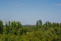 The landscape of the industrial city, green trees and mine waste. Heaps on a warm summer day stock photo