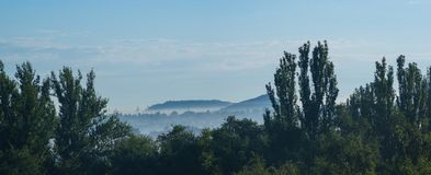 The landscape of the industrial city, green trees and mine waste. Heaps on a warm summer day royalty free stock image