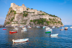 Landscape of Ischia port with Aragonese Castle. Coastal landscape of Ischia port with Aragonese Castle and anchored wooden boats Stock Images