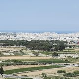 Landscape of island of Malta. Rural landscape with asphalt roads and fields on Malta. Maltese city on the background of Mediterranean sea Stock Photography