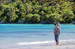 Landscape of Karikari Peninsula New Zealand. Man hold his child on Rangiputa beach in Karikari Peninsula Northland,New Zealand.It's a famous holiday travel stock photo