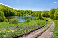Landscape with lake among the forest. Countryside road down the hill. photographer observes beautiful scenery in mountains. fine springtime weather Stock Photos
