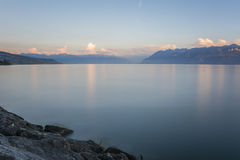 Landscape of lake geneva and mountains (alps) at sunset. Lake Geneva viewed from Lausanne on a summer evening - long exposure shot for a smooth water effect. In Stock Photos
