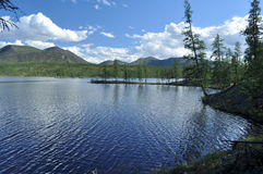 Landscape with a lake and mountains along the banks. Eastern Yakutia. Summer landscape with a lake and mountains along the banks Stock Photography