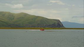 Landscape with lake and mountains. Coast guard floats in rubber boat stock video footage