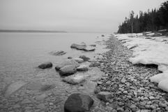 Landscape of lake shoreline with snow and stones bw Royalty Free Stock Photography