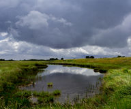 Landscape of lake and stormy sky. Lake and stormy sky with reflection,Saltfleet,Linconshire UK Stock Image