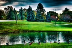 Landscape of lake and trees. With moody sky overhead Stock Image
