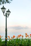 Landscape with latern, sea, flowers and grass. Beautiful landscape with sunset and latern. Flowers and grass in the front. Sea on the back Stock Photos