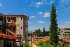 Landscape with laundry-drying in Tbilisi. Typical georgian landscape from courtyard with colored laundry-drying, cupressuses and ancient cathedral on background stock photography