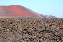 Spectacular landscape of lava fields and red volcano, Lanzarote, Spain Stock Photo