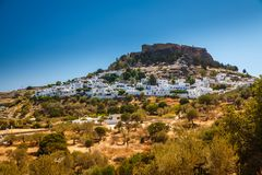Landscape with Lindos village. Landscape with the ancient Acropolis and white houses in Lindos, Rhodes, Greece royalty free stock images