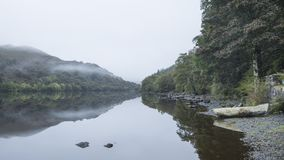 Landscape of Llyn Crafnant during foggy Autumn morning in Snowdo Stock Image