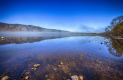 Landscape of Loch Ness in the early morning. Fog and reflection is adding to the picture mystical atmosphere. Scotland, UK Royalty Free Stock Photo