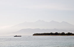 Landscape of Lombok Island. A beautiful view of Mount Rinjani. Silhouette of a boat passing by. Shot from Gili Trawangan Royalty Free Stock Image
