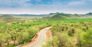 Landscape. Lone motorcycle rider passing through the Aravali hill landscape in Rajasthan state of India Royalty Free Stock Images
