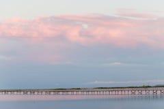 Landscape long bridge over a sea plait on a beautiful pink sunse Stock Photo