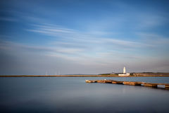 Landscape long exposure of lighthouse and jetty during Summer su Royalty Free Stock Image