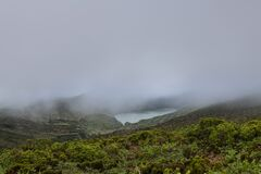 Landscape of low clouds and bad weather over Lagoa Funda das Lajes caldera volcanic crater lake at Ilha das Flores island in the