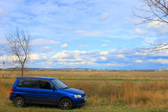 Landscape and the machine. The car stopped in the autumn field near a small town Royalty Free Stock Photo