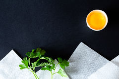 Landscape made up of broken eggs, parsley and white napkins Stock Images