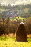 Landscape from Maramures - Romania. Romanian landscape from Maramures ( in the north of the country ) with haystack, houses and smoke Royalty Free Stock Image