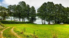 Landscape of Masuria in Poland. Warmian-Masurian region in northern Poland. View on field and Juksty lake near Czerwonki and MrÄ…gowo. Green meadows. trees stock image