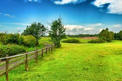 Landscape of Masuria in Poland. Warmian-Masurian region in northern Poland. View on field road, wooden fence and green meadows. village and countryside climate royalty free stock photos