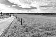 Landscape with meadow and pasture. Country road between spring fields with green grass in Belgium. Belgian landscape with meadow and pasture. Black and white royalty free stock images