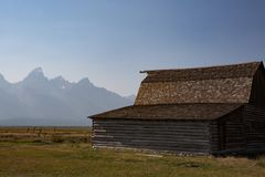 Grass field with barn and Grand Teton Mountains in background royalty free stock images